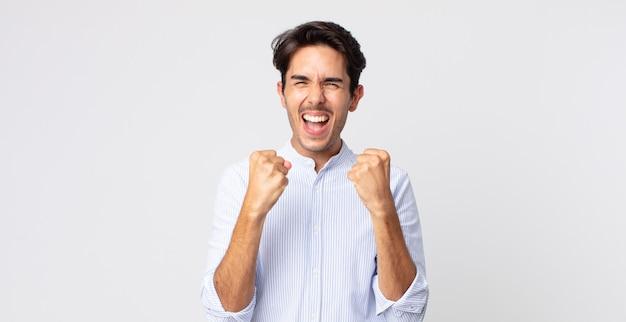 Przystojny hiszpan krzyczy triumfalnie, śmieje się, jest szczęśliwy i podekscytowany podczas świętowania sukcesu