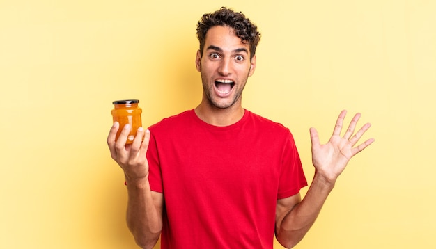 Przystojny hiszpan, który czuje się szczęśliwy i zdumiony czymś niewiarygodnym. dżem brzoskwiniowy