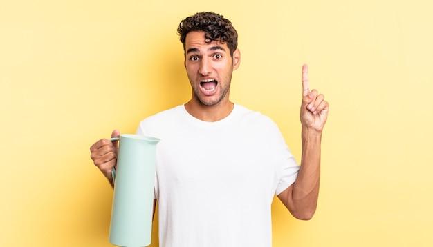 Przystojny hiszpan, który po zrealizowaniu pomysłu czuje się jak szczęśliwy i podekscytowany geniusz. koncepcja termosu do kawy