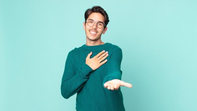 Przystojny hiszpan, szczęśliwy i zakochany, uśmiechający się jedną ręką przy sercu, a drugą wyciągniętą do przodu