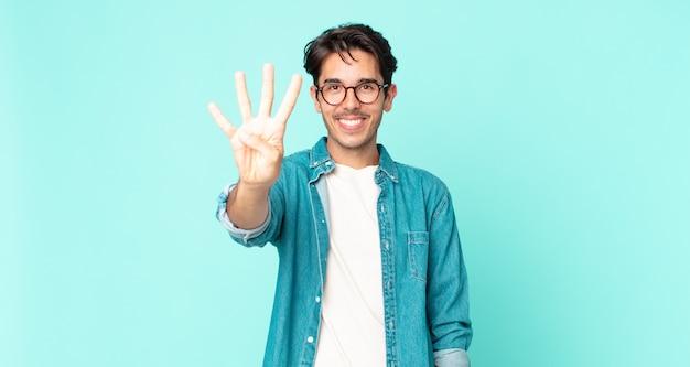 Przystojny hiszpan uśmiechający się i wyglądający przyjaźnie, pokazujący cyfrę cztery lub czwartą z ręką do przodu, odliczający w dół