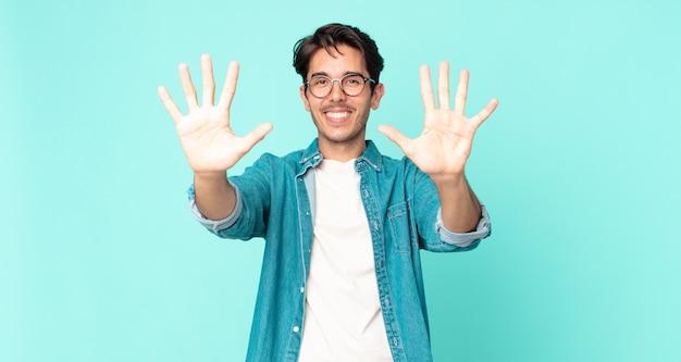 Przystojny hiszpan uśmiechający się i wyglądający przyjaźnie, pokazujący cyfrę dziesiątą lub dziesiątą z ręką do przodu, odliczając w dół