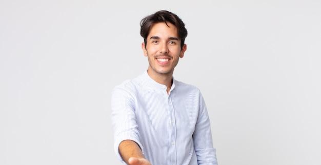 Przystojny hiszpan uśmiechnięty, wyglądający na szczęśliwego, pewnego siebie i przyjazny, oferujący uścisk dłoni w celu zawarcia transakcji, współpracujący