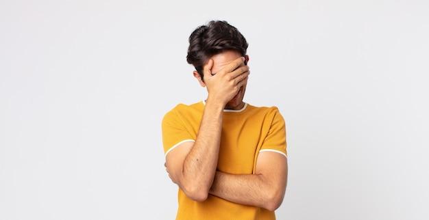 Przystojny hiszpan wyglądający na zestresowanego, zawstydzonego lub zdenerwowanego, z bólem głowy, zakrywający twarz dłonią