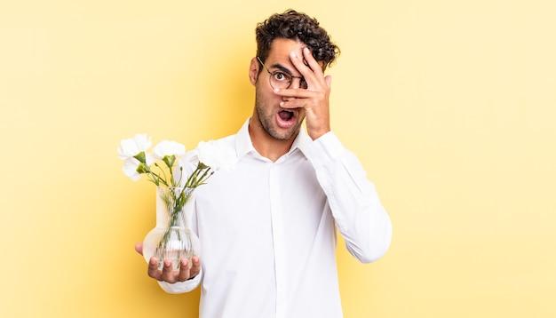 Przystojny hiszpan wyglądający na zszokowanego, przestraszonego lub przerażonego, zakrywający twarz dłonią. koncepcja doniczki z kwiatami