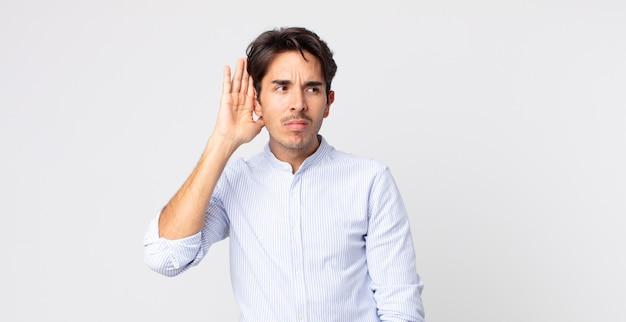 Przystojny hiszpan wyglądający poważnie i zaciekawiony, słuchający, próbujący usłyszeć tajną rozmowę lub plotki, podsłuchujący