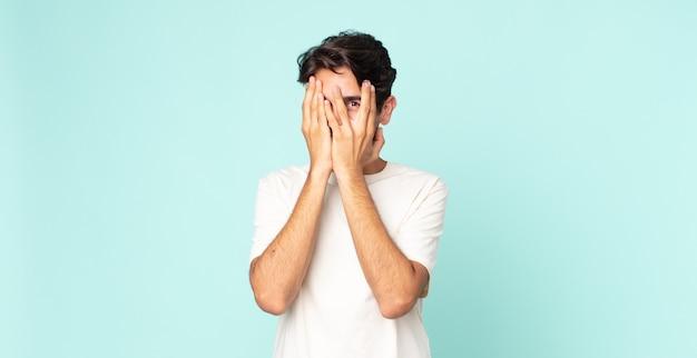 Przystojny hiszpan zakrywający twarz dłońmi, zerkający między palcami ze zdziwionym wyrazem twarzy i patrzący w bok