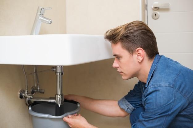 Przystojny hydraulik naprawia odciek zlew