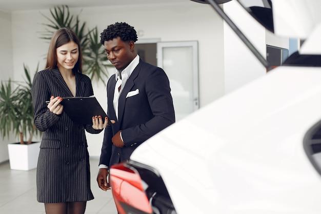 Przystojny i elegancki murzyn w salonie samochodowym