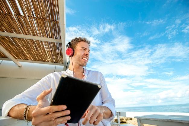 Przystojny i odnoszący sukcesy kaukaski mężczyzna słuchanie muzyki na plaży. praca niezależna i zdalna. student na wybrzeżu morza śródziemnego