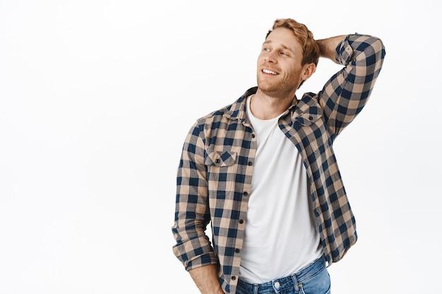Przystojny i pewny siebie mężczyzna macho z rudymi włosami i silnymi ramionami, trzymający ręce za głową, patrzący na bok i uśmiechnięty zadowolony, odpoczywający, relaksujący się na białej ścianie