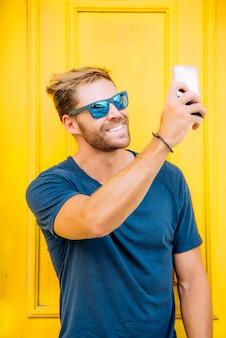 Przystojny i przy użyciu telefonu komórkowego i noszących okulary przeciwsłoneczne