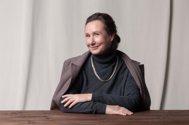 Przystojny i stylowy kaukaski starsza bizneswoman siedzi przy stole i uśmiecha się.