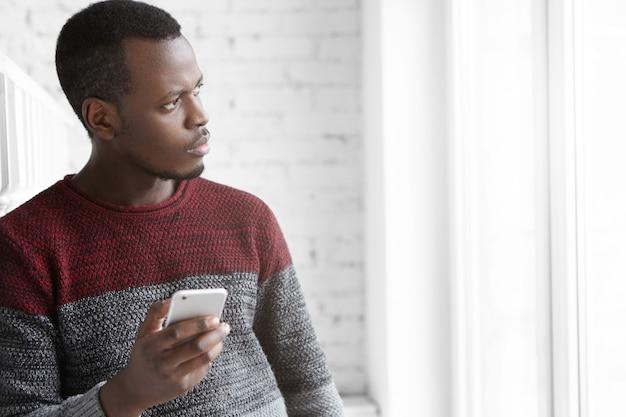 Przystojny i zamyślony młody student afroamerykanów w wygodnym swetrze