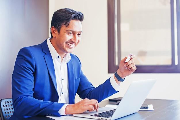 Przystojny indyjski mężczyzna płaci za swoje zamówienie online