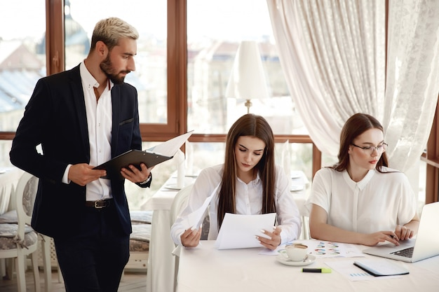 Przystojny inspektor restauracji z dokumentami i dwoma asystentkami