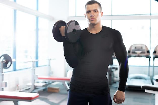 Przystojny instruktor fitness pozowanie z hantle w siłowni