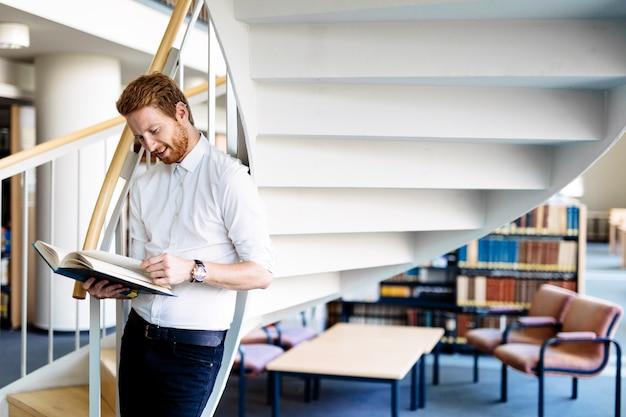 Przystojny inteligentny facet czyta książkę w bibliotece