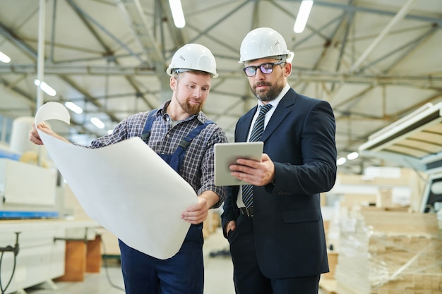 Przystojny inwestor pokazuje dane online inżynierowi