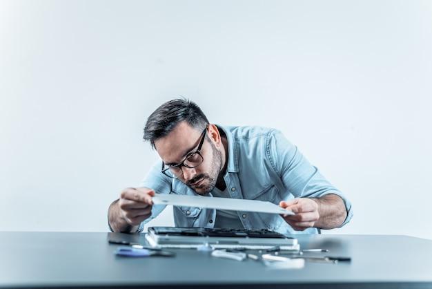 Przystojny inżynier montuje naprawiającego laptop.