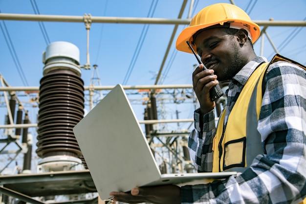 Przystojny inżynier posiadający papierowe projekty planowania i używający walkie talkie przed elektrownią dużej mocy. widok wykonawcy z tyłu na tle budynków elektrowni.