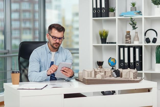 Przystojny inżynier pracuje nad projektem budowlanym, ogląda makietę przyszłego budynku i robi notatki na komputerze typu tablet