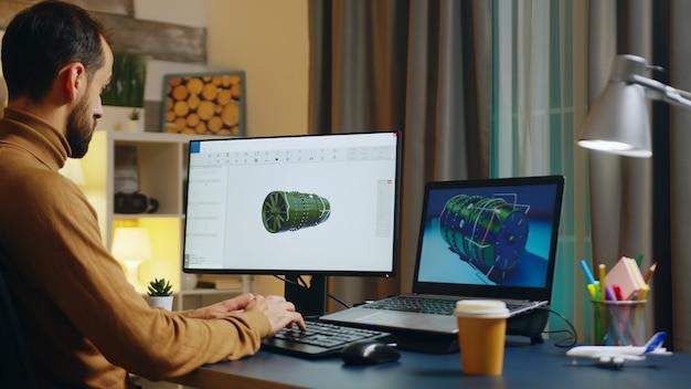 Przystojny inżynier w swoim domowym biurze opracowuje nową turbinę. kreatywny freelancer.