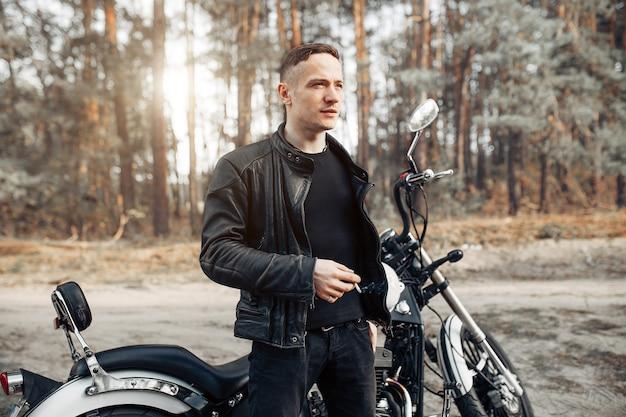 Przystojny jeźdza facet w czarnej rowerzysta kurtce na klasyka setkarza cukiernianym motocyklu przy zmierzchem
