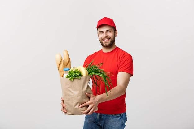 Przystojny kaukaski doręczeniowy mężczyzna niesie pakunek torbę sklepu spożywczego jedzenie i napój od sklepu.