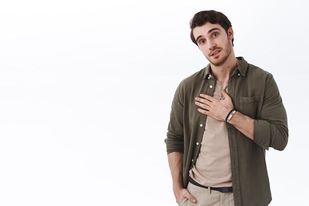 Przystojny kaukaski facet jest szczery, mówi prawdę, trzymając rękę na klatce piersiowej, aby wyrazić swoje szczere uczucie