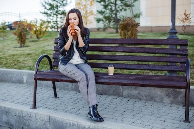 Przystojny kaukaski kobieta siedzi w parku i jedzenie rogalika