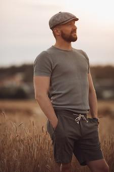 Przystojny kaukaski mężczyzna o mocnym ciele i ciemnej brodzie w szarej koszulce, spodenkach i czapce na polu