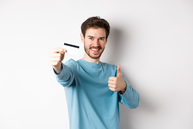 Przystojny kaukaski mężczyzna pokazując plastikową kartę kredytową z kciuk w górę, polecam i chwalą dobrą ofertę banku, stojąc na białym tle.
