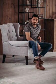Przystojny kaukaski mężczyzna w szarej koszulce, niebieskich dżinsach i brązowych butach, siedząc na szarym fotelu i patrząc w kamerę