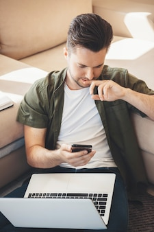 Przystojny kaukaski mężczyzna z brodą, rozmawiając na telefon komórkowy i trzymając laptopa siedząc na podłodze