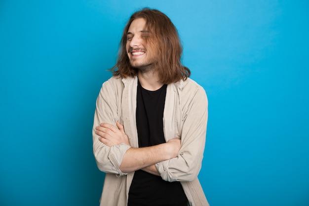 Przystojny kaukaski mężczyzna z długimi włosami i brodą, uśmiechając się ze skrzyżowanymi rękami na niebieskiej ścianie