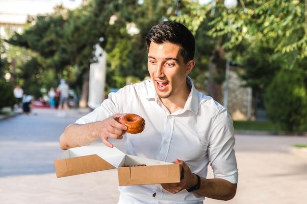 Przystojny kaukaski młody mężczyzna w białej koszuli, ciesząc się pysznym karmelowym pączkiem w parku miejskim.