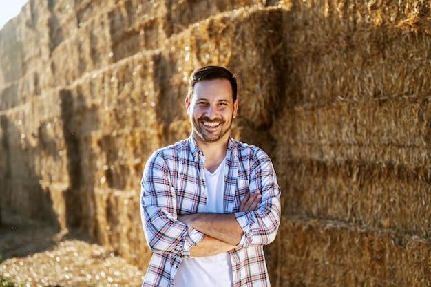Przystojny kaukaski uśmiechnięty rolnik stojący na zewnątrz z rękami skrzyżowanymi