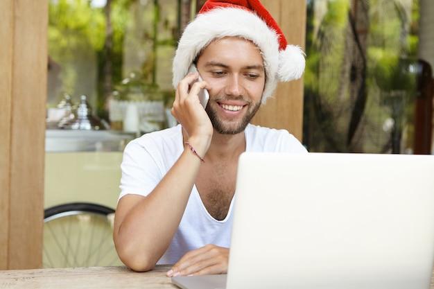 Przystojny kaukaski w czapce świętego mikołaja rozmawia przez telefon komórkowy, siedzi przed otwartym laptopem, uśmiecha się, ma radosny wyraz twarzy, ciesząc się wakacjami noworocznymi daleko w gorącym kraju
