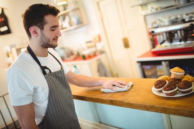 Przystojny kelner czyszczenia licznika