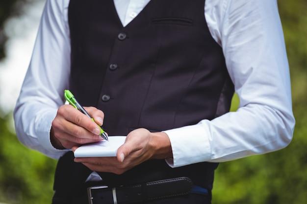 Przystojny kelner piszący zamówienie