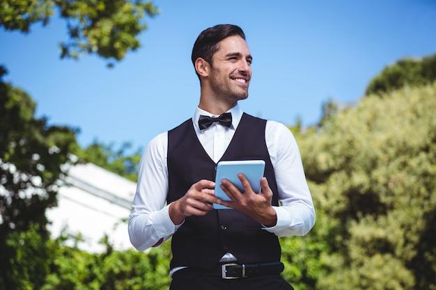 Przystojny kelner przy użyciu komputera typu tablet