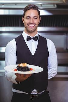 Przystojny kelner trzyma talerz spaghetti atramentu kałamarnicy