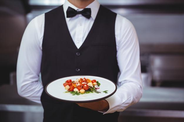Przystojny kelner trzyma talerza