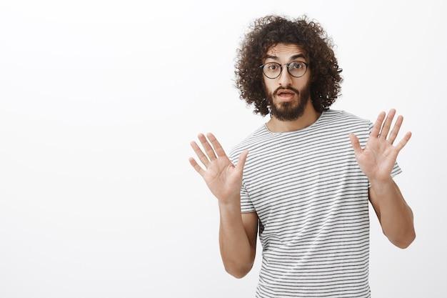 Przystojny, kreatywny, brodaty latynoski kolega ze stylowej fryzury, unoszący dłonie, kształtując coś podczas rozmowy