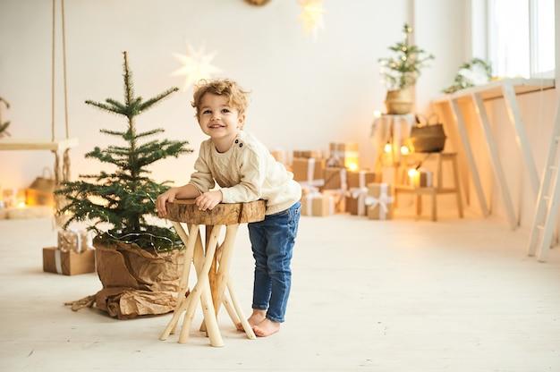 Przystojny, kręcony chłopiec siedzi na drewnianym krześle w pobliżu choinki
