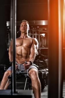 Przystojny kulturysta robi ciężkie ćwiczenia na plecy na symulatorze. wysportowana sylwetka, przygotowanie do sezonu letniego. motywacja fitness. skopiuj miejsce, baner sportowy.