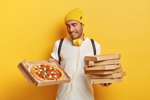 Przystojny kurier z pudełkami po pizzy
