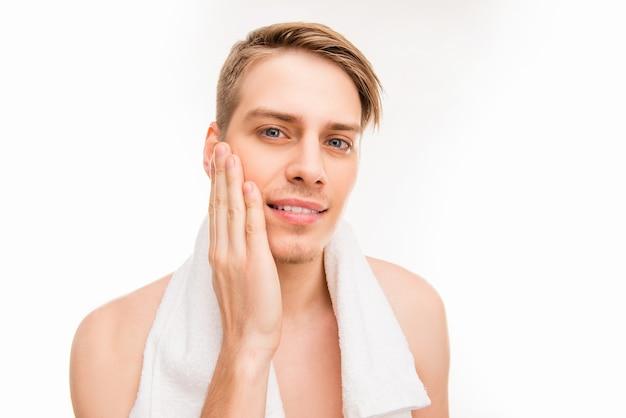 Przystojny ładny młody człowiek z ręcznikiem dotyka jego twarzy po goleniu