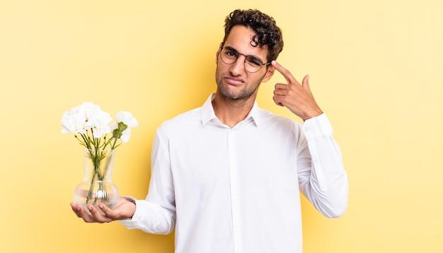 Przystojny latynos czuje się zdezorientowany i zdezorientowany, pokazując, że jesteś szalony. koncepcja doniczki z kwiatami